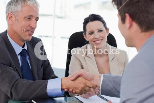 Smiling business team concluding an agreement with a client