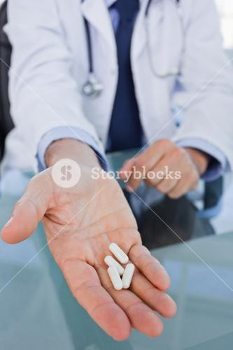 Portrait of a hand showing pills
