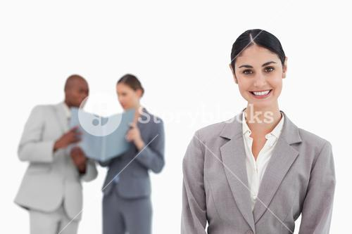 Smiling saleswoman with coworkers behind her