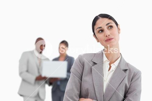 Daydreaming businesswoman with colleagues behind her