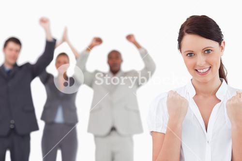 Victorious businesswoman with cheering team behind her
