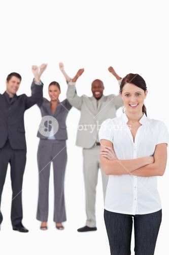 Smiling businesswoman with cheering coworkers behind her