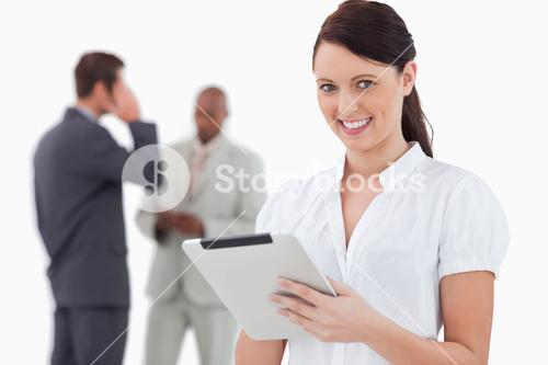 Tradeswoman with tablet and associates behind her