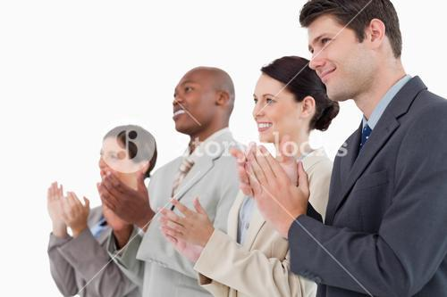 Side view of applauding sales team standing together