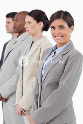 Smiling businesswoman standing next to her associates