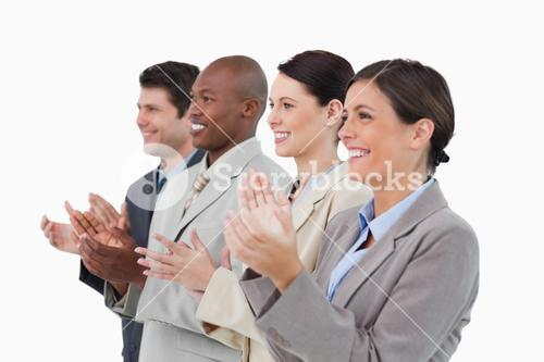 Side view of clapping sales team standing together
