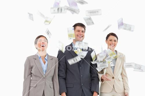 Money falling down on smiling business team