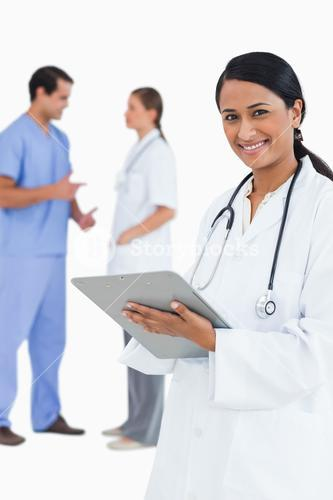 Smiling doctor with clipboard and staff members behind her