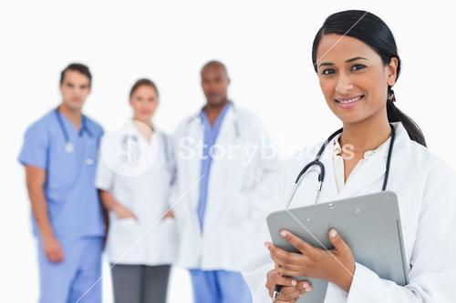 Female doctor with clipboard and staff members behind her