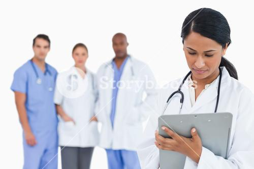 Female doctor taking notes on clipboard with staff members behind her