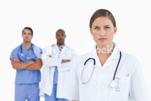Female doctor with male colleagues behind her