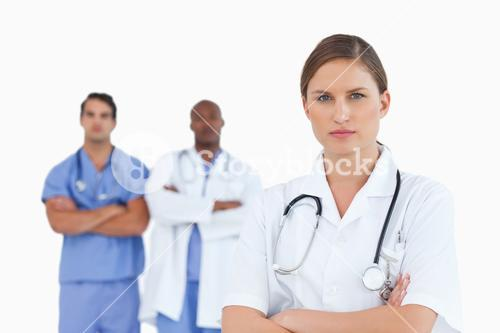Female doctor with folded arms and male colleagues behind her