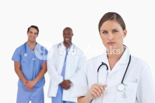 Serious looking female doctor with male colleagues behind her