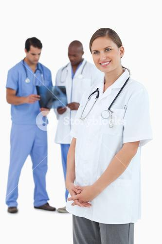 Smiling doctor with colleagues and xray behind her