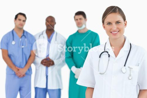 Female doctor with colleagues behind her
