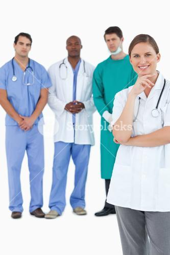 Smiling doctor with male staff members behind her