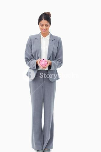 Smiling bank assistant with piggy bank