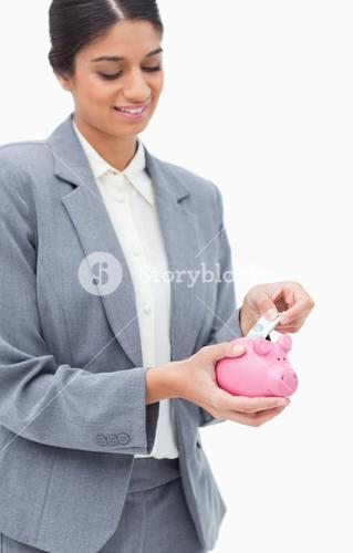 Smiling bank employee putting bank note into piggy bank
