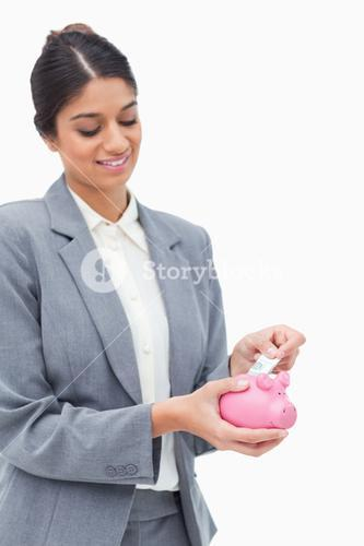 Smiling bank assistant putting bank note into piggy bank