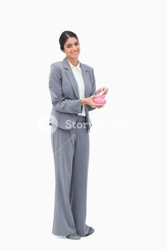 Smiling female banker putting money into piggy bank