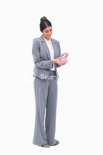 Smiling female banker putting bank note into piggy bank