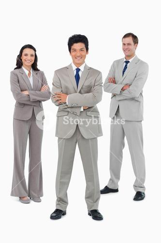 Smiling sales team with folded arms