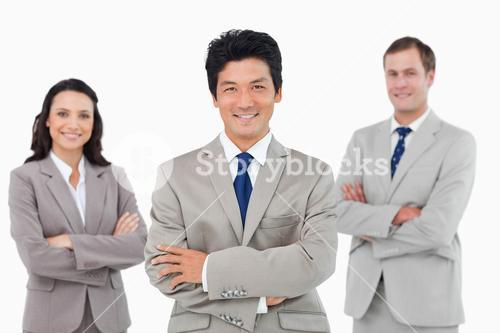 Smiling sales team with arms folded