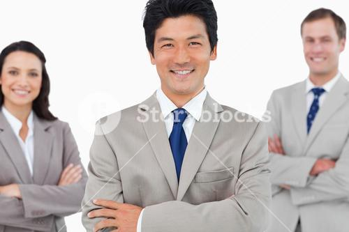 Smiling sales team with arms crossed
