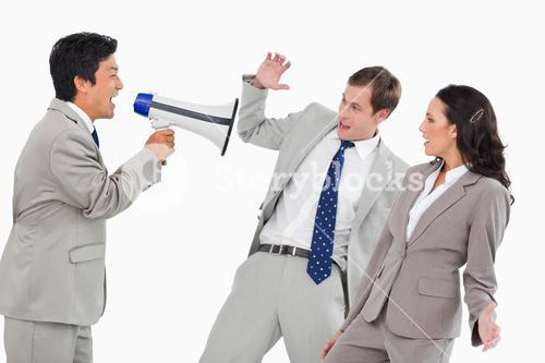 Businessman with megaphone yelling at colleagues