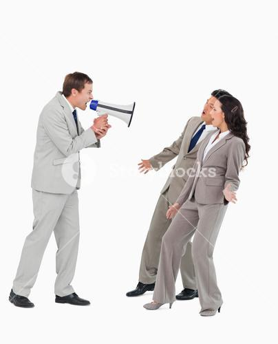 Businessman with megaphone yelling at associates