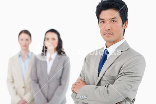 Confident businessman with employees behind him