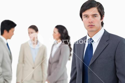 Young businessman with talking associates behind him