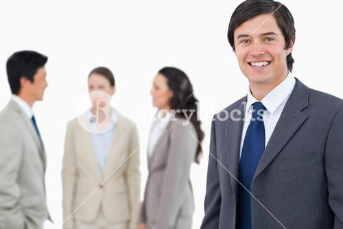 Smiling young businessman with talking associates behind him