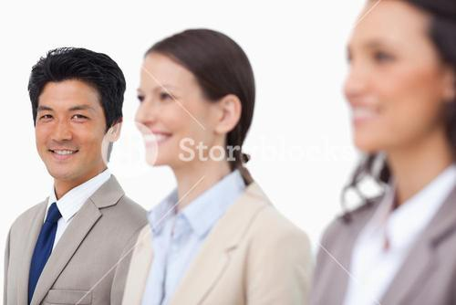Smiling salesman standing next to smiling colleagues