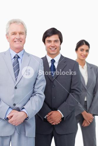 Smiling mature businessman with young employees