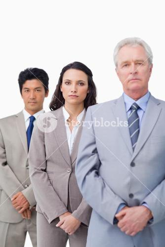 Mature salesman standing with his young employees