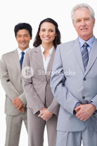 Mature businessman standing with employees