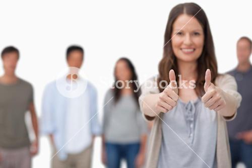 Thumbs up given by smiling woman with friends behind her