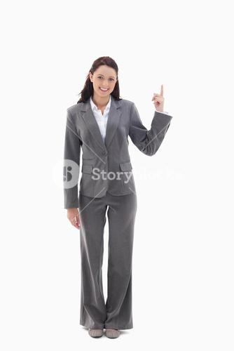 Businesswoman smiling and pointing up