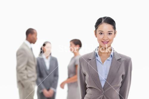 Businesswoman smiling with coworkers in the background