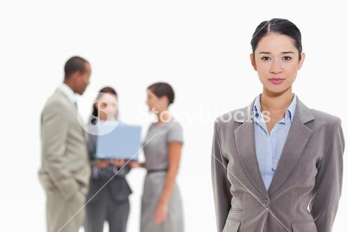 Serious businesswoman with coworkers in the background