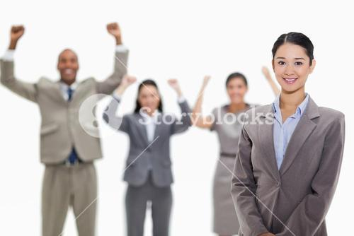 Businesswoman smiling with enthusiastic coworkers