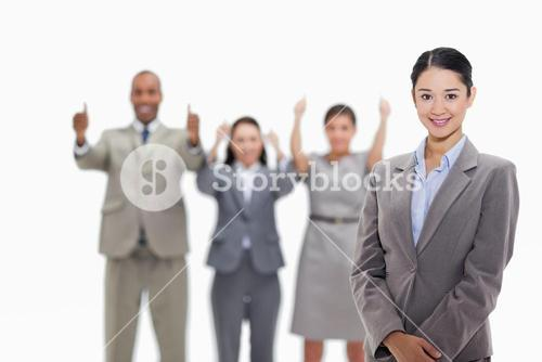 Businesswoman smiling with coworkers approving in the background