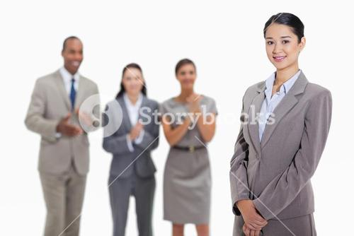 Businesswoman with coworkers applauding in the background