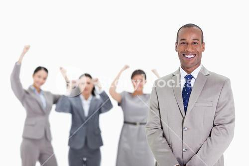 Happy businessman with enthusiastic coworkers in the background