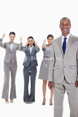 Happy businessman with approving coworkers in background
