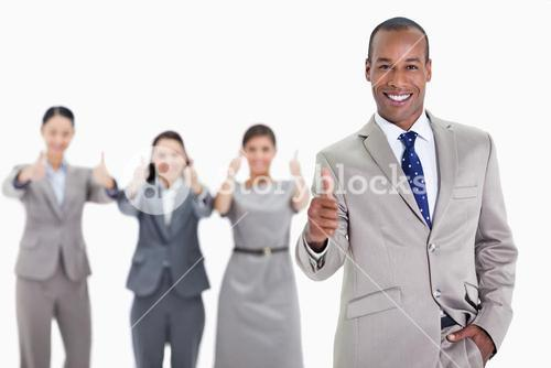Happy businessman with coworkers in the background with thumbs up