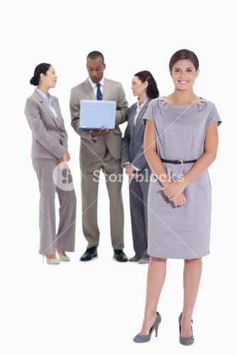 Woman holding her hands with coworkers talking in the background