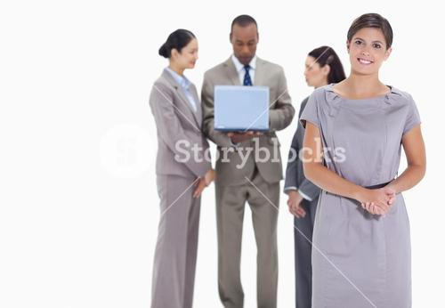 Woman welcoming and coworkers with a laptop in the background