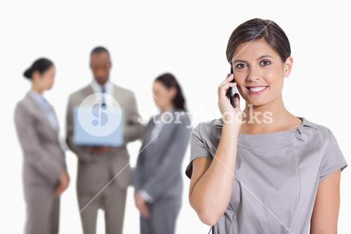 Woman with her head tilted slightly smiling on the phone and coworkers with a laptop